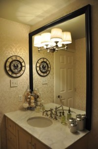 This bathroom mirror is only framed on 3 sides with the bottom edge resting on the countertop. A hole was made in the mirror to incorporate the lighting fixture.